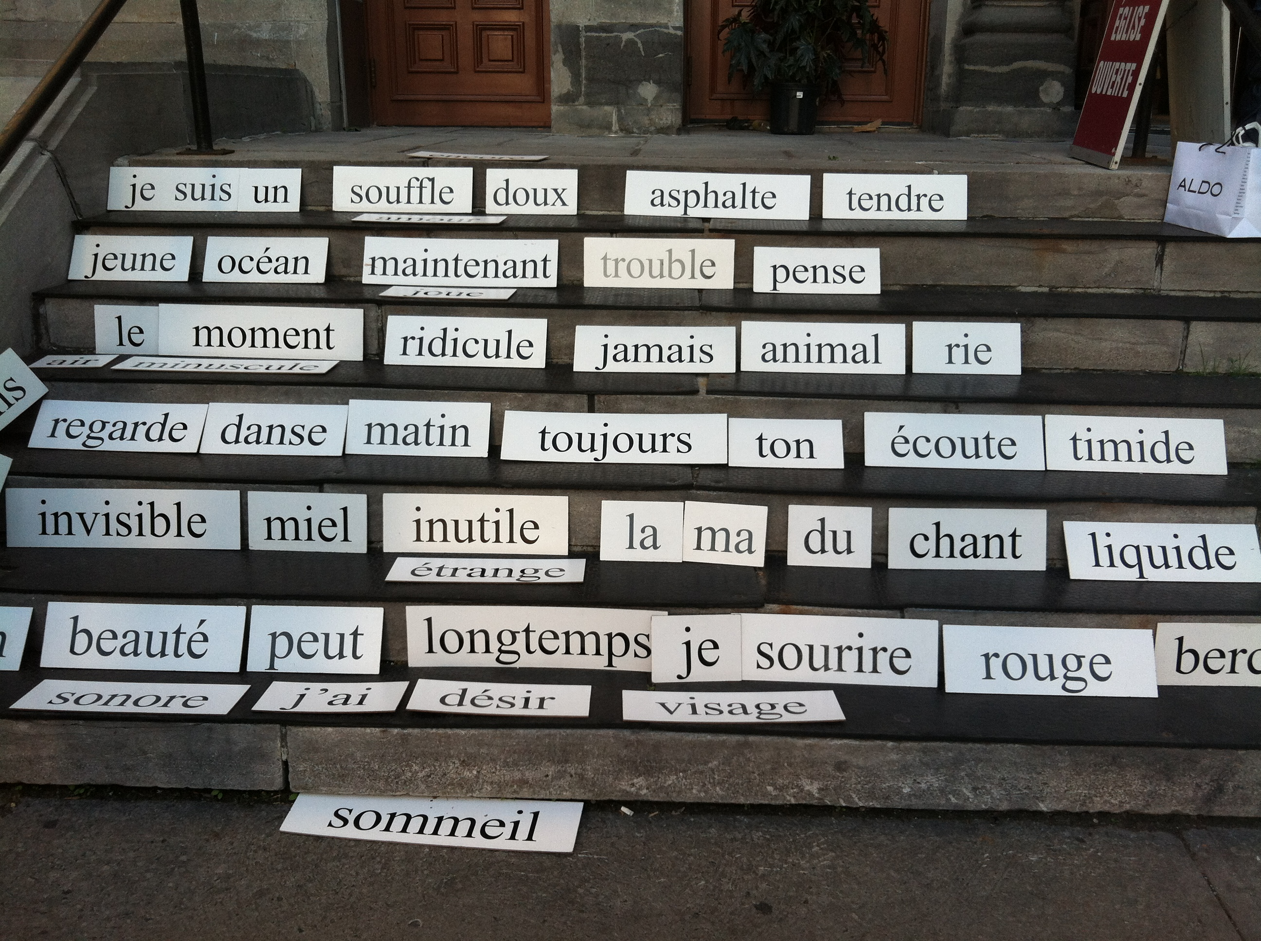 French words on panels on a stairway.